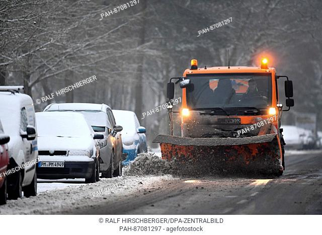 A winter service snow clearer is shovelling away freshly fallen snow from the streets of Kleinmachnow, Germany, 8 January 2017