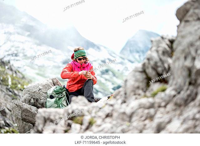 Young female hiker having a break in the near of the Muttlerkopf in the Alps