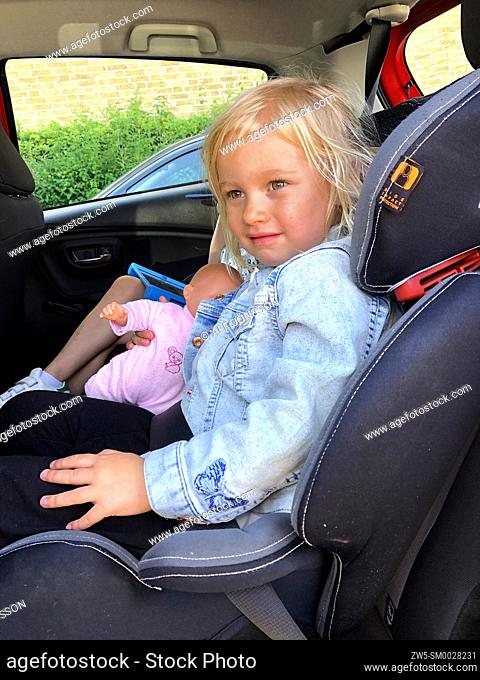Tree years old girl sit in a safety car seat