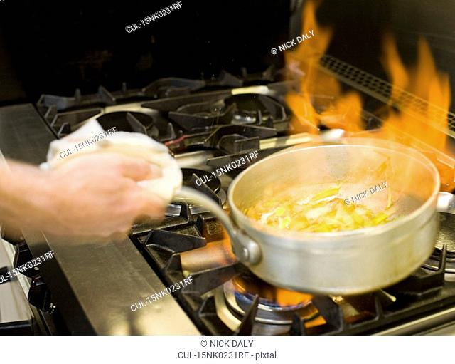 A flaming pan cooking on a hob