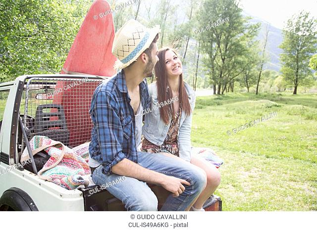 Friends sitting on back of off road vehicle