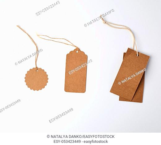 round and rectangular brown paper price tags hanging on a rope, white background