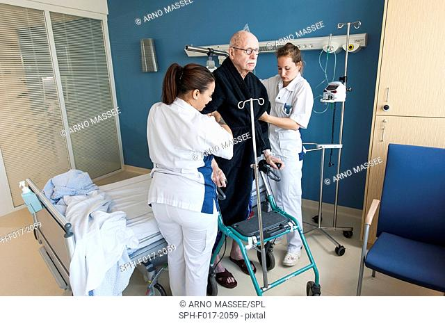 MODEL RELEASED. Female nurses helping senior male in hospital ward