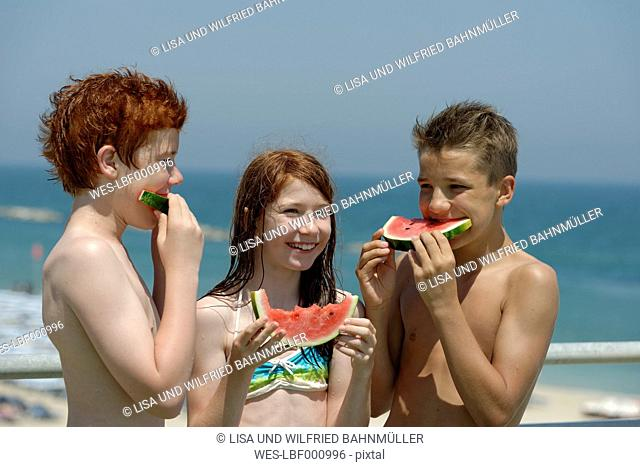 Italy, girl and two teenage boys eating watermelon slices at the beach