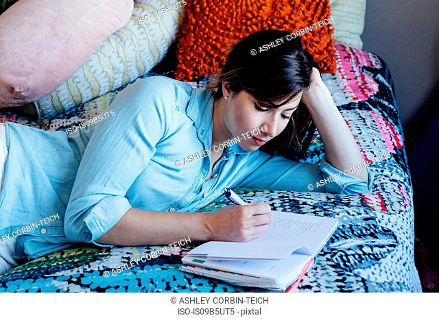 Young woman lying on shabby chic bed writing in notebook