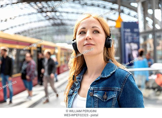 Portrait of woman listening to music with headphones at the station, Berlin, Germany
