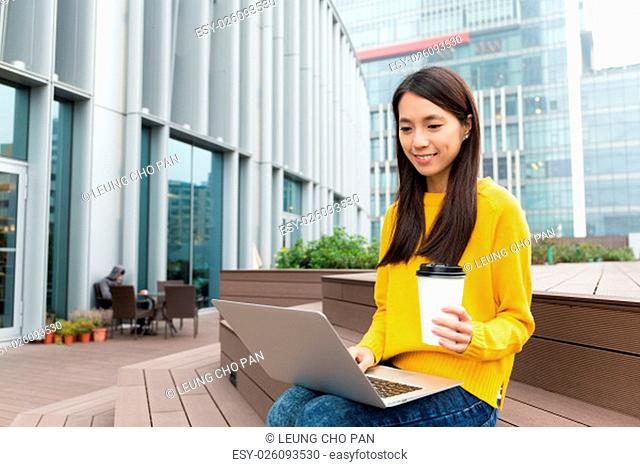 Beautiful Woman use of the laptop computer with warm coffee at outdoor