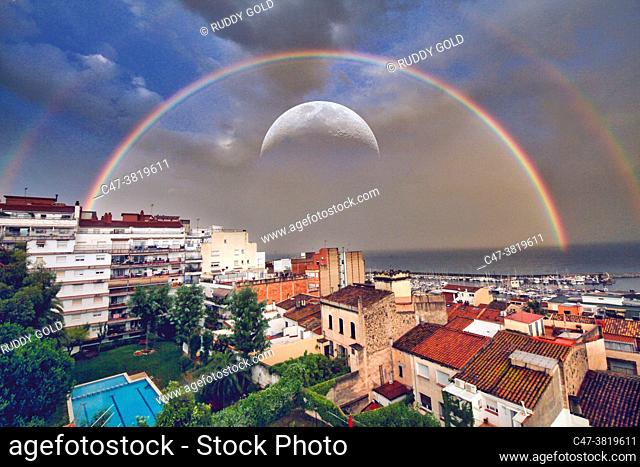 Double rainbow and big moon over the residential area of El Masnou. Barcelona. El Masnou is a municipality in the province of Barcelona