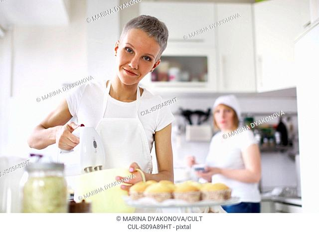 Woman using electric whisk