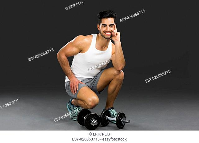 Portrait of handsome young man lifting weights, isolated over a gray background