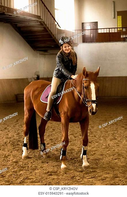 young female jockey siting on brown horse in riding hall