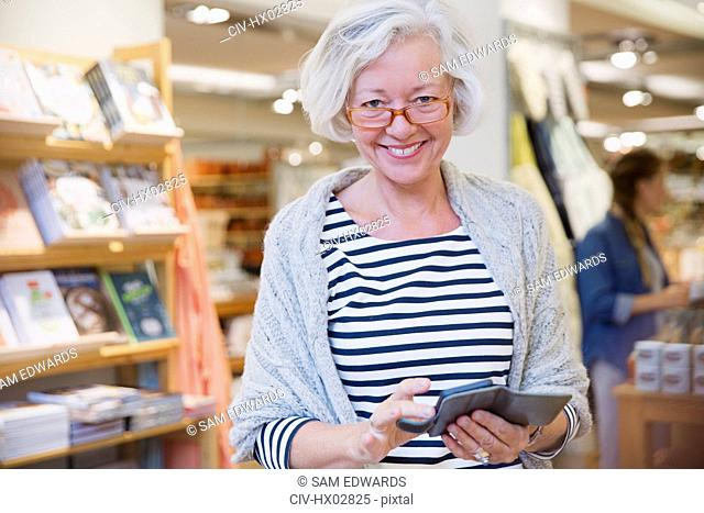 Portrait smiling mature female shopper using cell phone in shop
