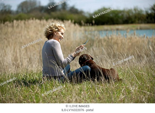 A mature woman sitting in long grass with her dog, looking at a digital tablet