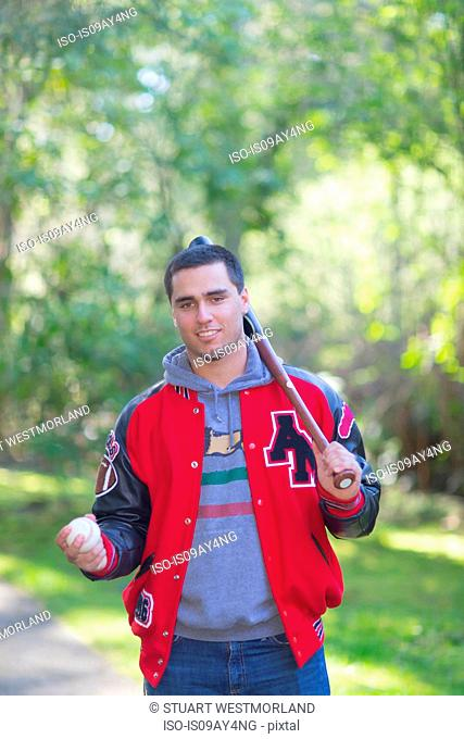 Portrait of high school senior wearing jacket, carrying baseball bat and ball in park