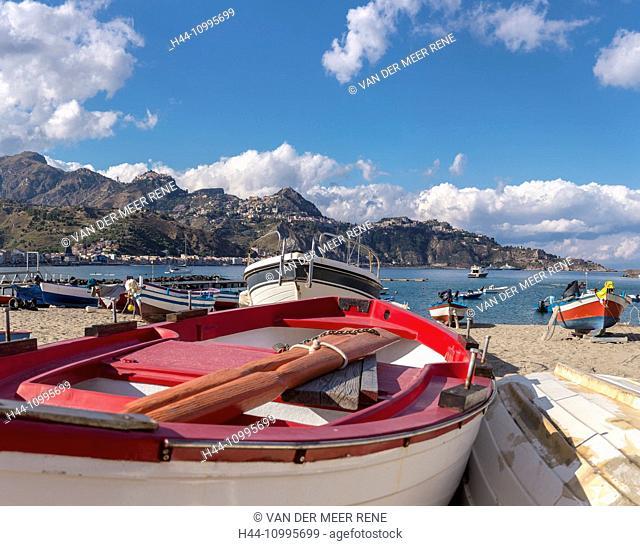 Fishing-boats at the beach, view towards Taormina on a mountain ridge