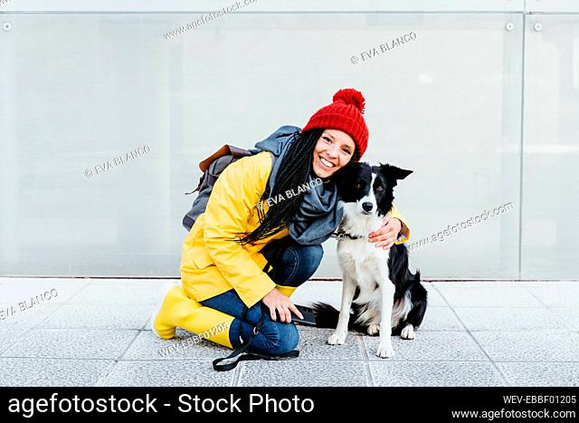 Smiling woman embracing dog while kneeling on footpath against wall