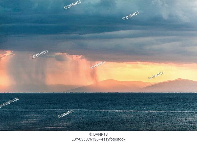 Rain pouring from clouds over distant plains near mountains with orange sun light at the horizon