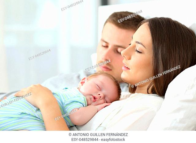 Portrait of tired parents sleeping with their baby on a bed at home