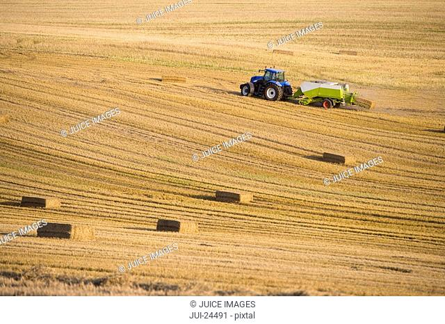 Tractor and straw baler in wheat field
