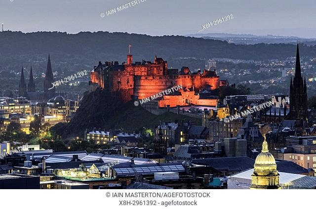 View of Edinburgh Castle illuminated in red in the evening from Salisbury Crags in Edinburgh, Scotland, United Kingdom