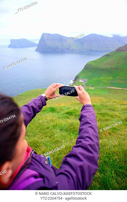 Young active woman hiking in Kalsoy takes photo with mobile phone, Faroe Islands