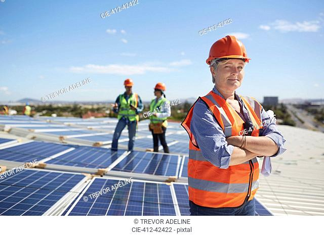 Portrait confident female engineer at sunny solar power plant