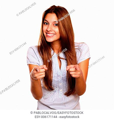 Portrait of a charming young woman with long brown hair looking and pointing at you against white background
