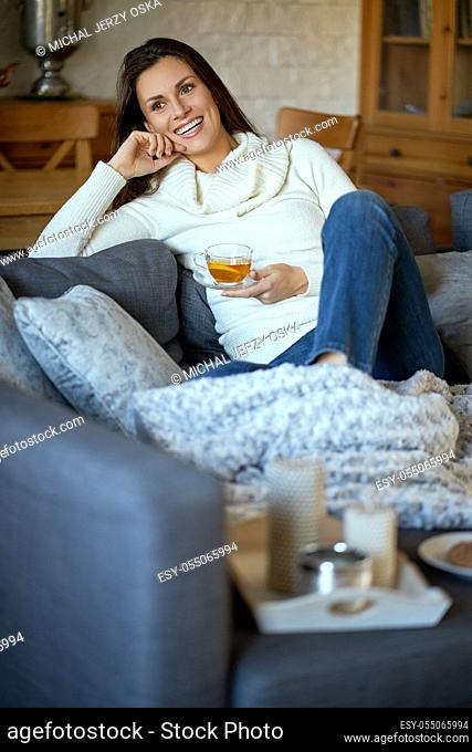 attractive young woman in sweater relaxes on a gray sofa at home and drinks tea with lemon
