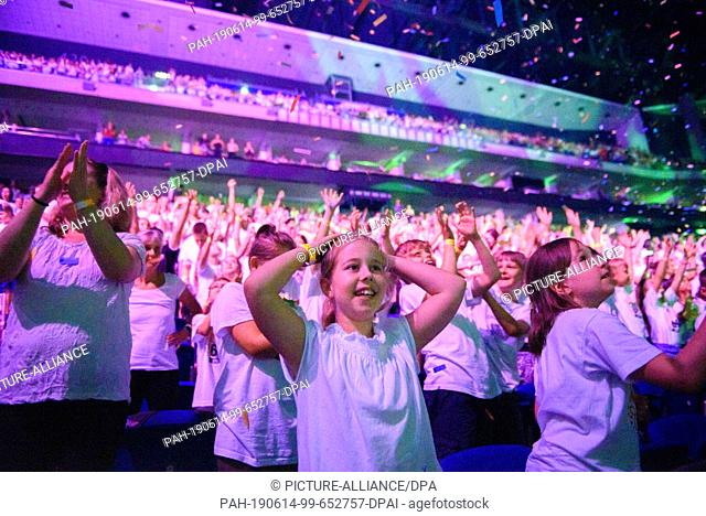 """14 June 2019, Berlin: Schoolgirls stand singing and dancing in the grandstand of the Mercedes-Benz Arena during the concert of """"""""6K United! The choir concert is..."""