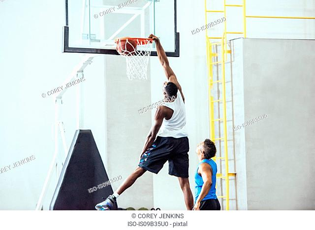 Male basketball player throwing ball into hoop on basketball court