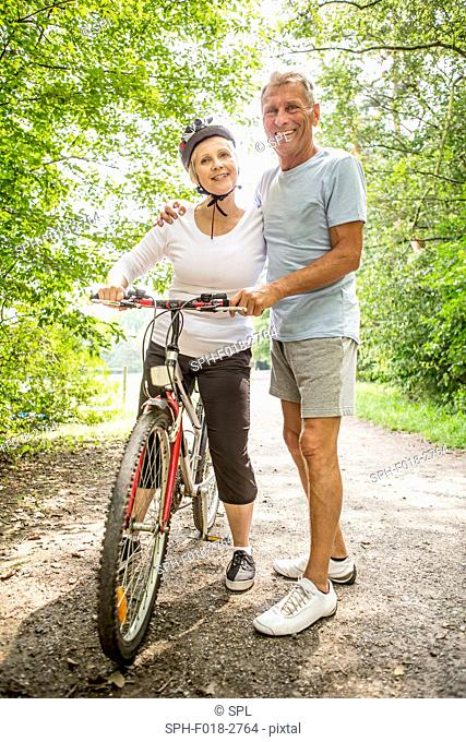 MODEL RELEASED. Mature woman on bike, senior man with arm around