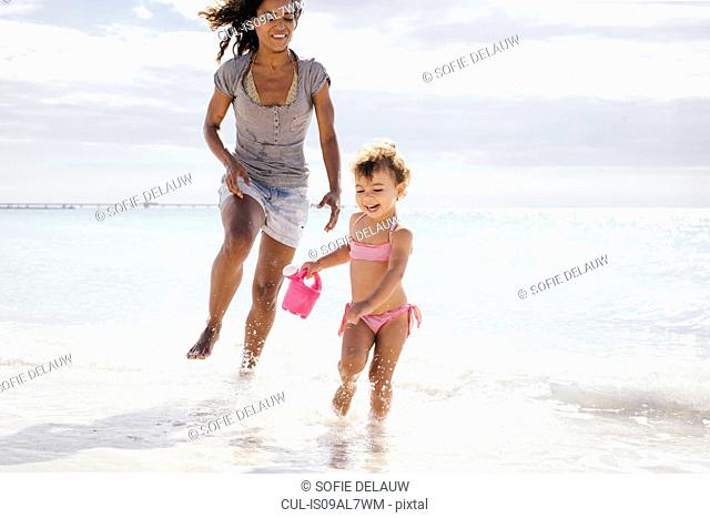 Mother and toddler daughter running with toy watering can on beach, Tuscany, Italy