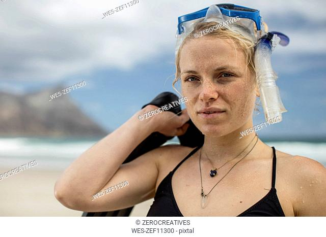 Portrait of young woman with snorkeling equipment on the beach