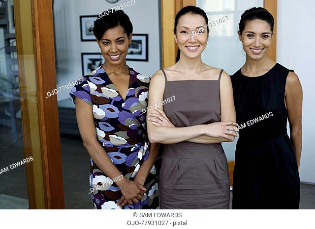 Three businesswomen in an office smiling