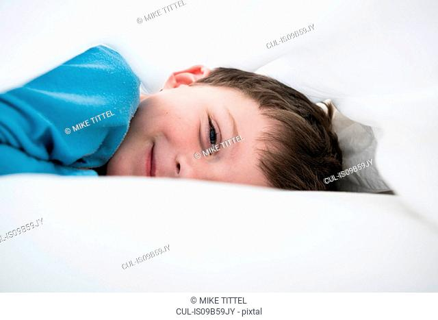 Portrait of boy lying between white bed sheets