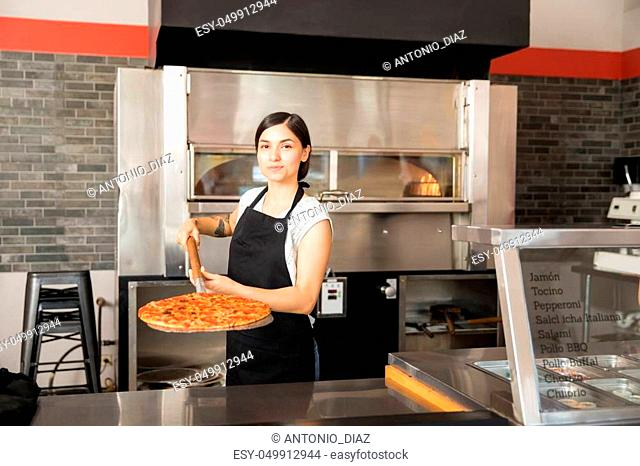 Beautiful woman chef wearing black uniform holding pizza peel with freshly baked pepperoni cheese pizza in hand while placing it on counter and looking at...