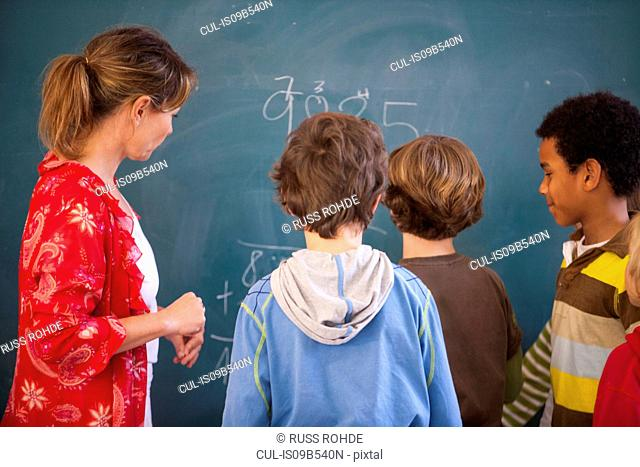 Primary school teacher teaching equations to boys at classroom blackboard