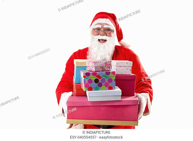 Front view of happy Santa Claus carrying Christmas gifts over white background