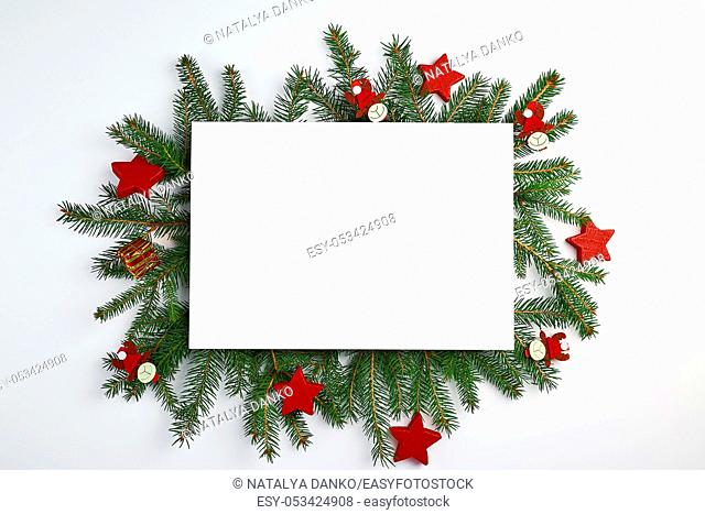 congratulatory Christmas background with an empty white sheet and green branches of spruce decorated with holiday toys on a white background, mock up
