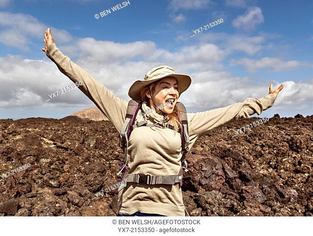 Happy woman hiking at Timanfaya National Park, Lanzarote, Canary Islands, Spain
