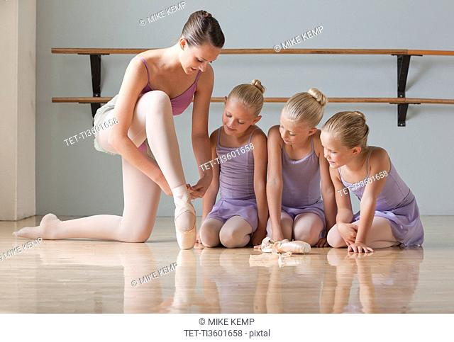Female instructor training ballet dancers 6-8 in dance studio