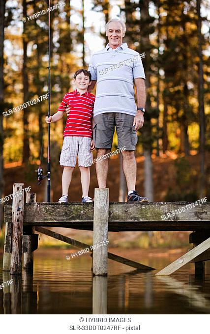 Boy with grandfather on jetty over lake