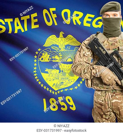 Soldier holding machine gun with USA state flag on background - Oregon