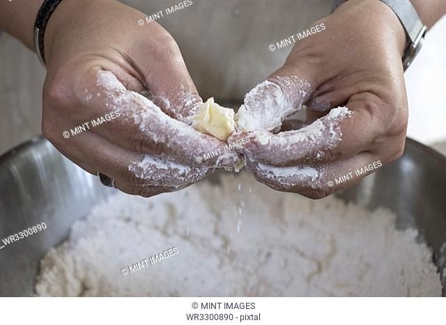 Close up of person rubbing in butter and flour for a crumble between her finger tips