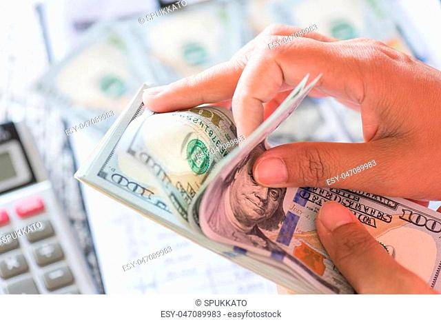 Close up woman hands holding and counting bunch of America dollars banknotes calculator and red pencil in background
