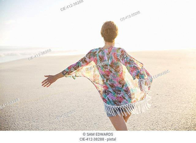 Carefree woman walking with arms outstretched on summer beach