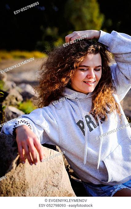 lovely young woman with curly hair, the romance of youth, a journey walk on a warm summer sunny day