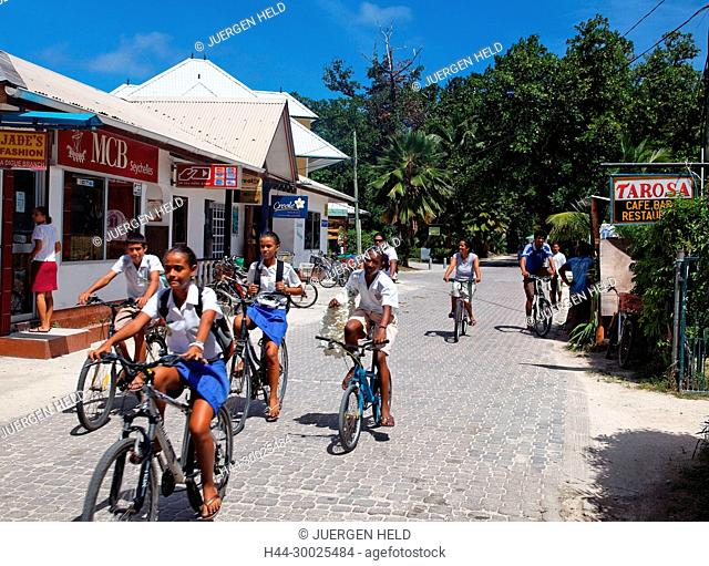 Pupils on bycycles on the main street of La Passe , La Digue, Seychelles, Indian Ocean, Africa