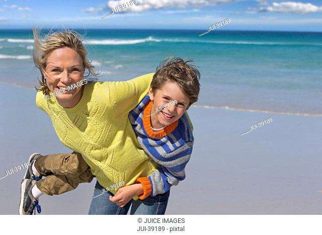 Portrait of happy mother and son playing on sunny beach