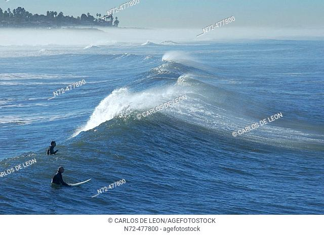 Morning summer surf session, guys waiting for the right wave. San Diego, California